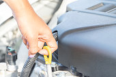 istock a wooman maintenance a car.  Check the engine oil level. 1030222336