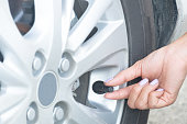istock a wooman maintenance a car.  Check the tire pressure. 1030222494