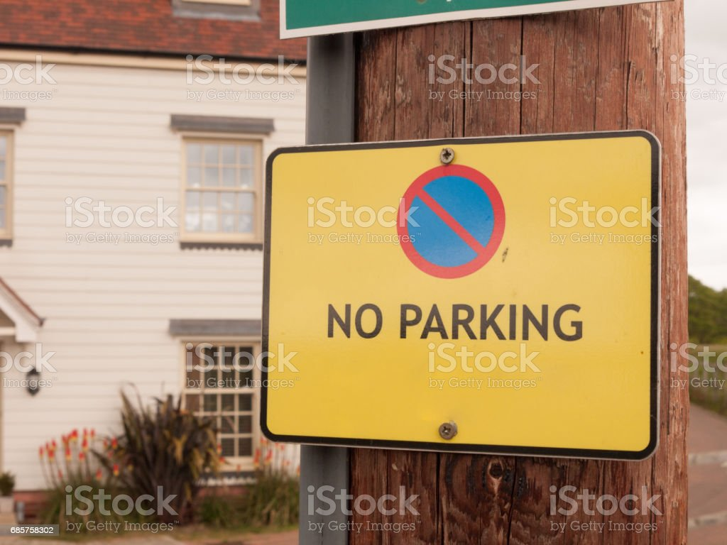a yellow warning traffic sign outside saying no parking allowed stock photo