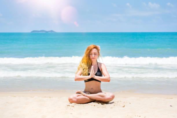 Ein junges, schönes Mädchen mit roten Haaren, in einem Bikini. praktiziert Yoga auf dem weißen Sand und dem türkisfarbenen Meer. – Foto