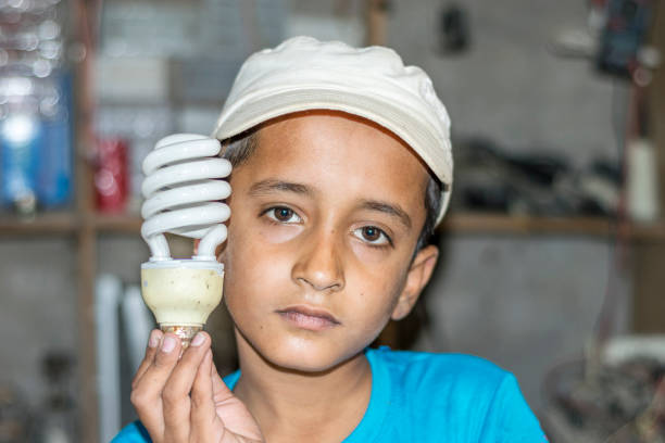 ein junger niedlicher junge hält eine glühbirne - kindergarten handwerk stock-fotos und bilder