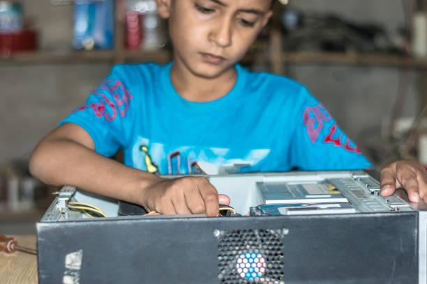 ein kleiner niedlicher junge repariert festplatte eines computers auf einem holztisch mit seinem werkzeug - kindergarten handwerk stock-fotos und bilder