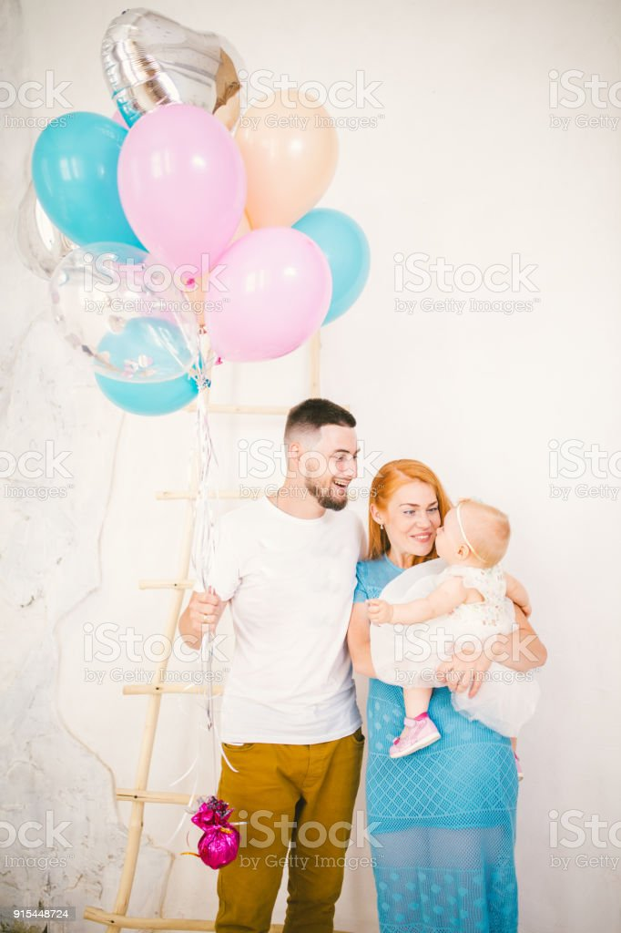 a young family of three people, mom's dad and daughter's one year old stands inside the room. Holding a balloon in her hand, a woman with red long hair is holding a child in her arms dressed in a white dress. Birthday party of a child stock photo