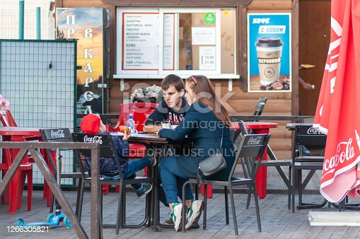 Petrozavodsk, Russia - 26 August 2019. a young family with a child sit at a table of a summer cafe