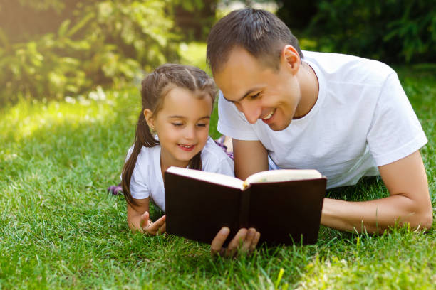 a young father with his little daughter reads the Bible stock photo