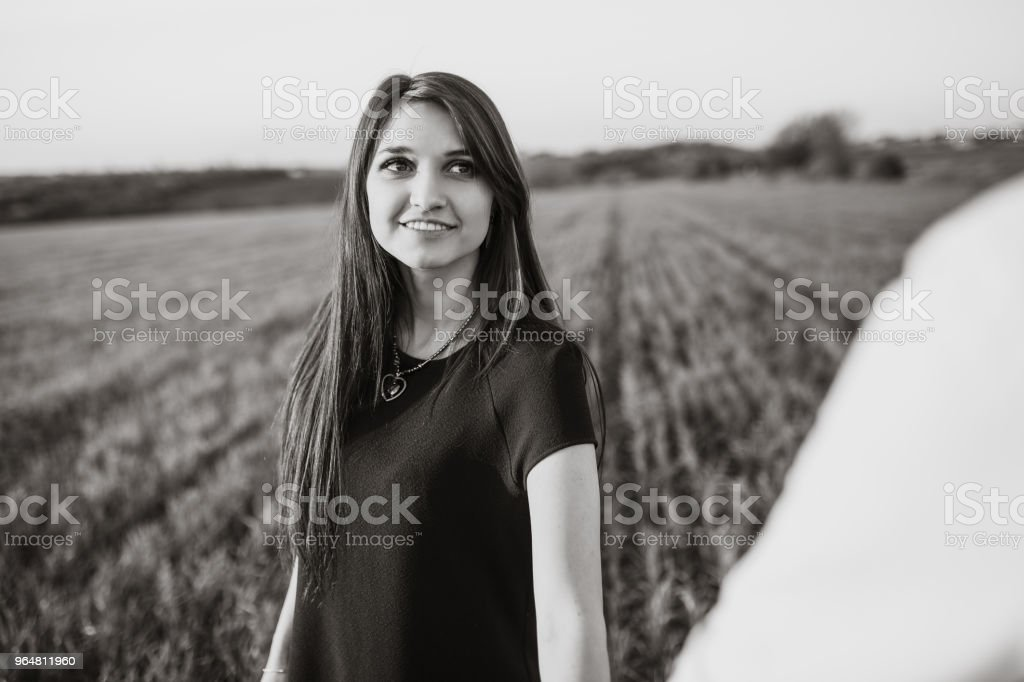 a young girl posing in the background of the field, looking at the other half, advertising and inserting text royalty-free stock photo