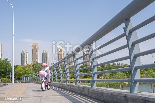a young girl riding bicycle on the road