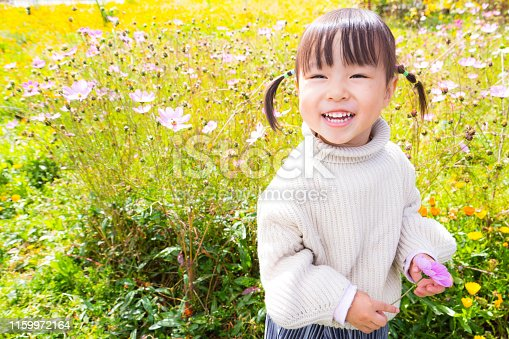 a young girl smiling in the flowers