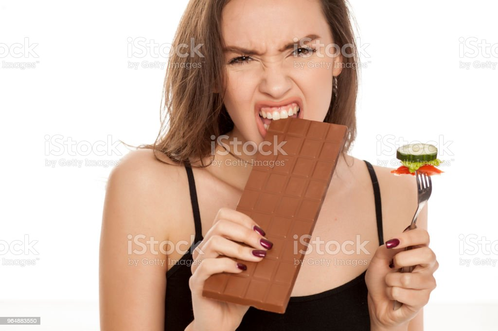 a young happy woman eating chocolate and hlod a fork with vegetable on white background royalty-free stock photo