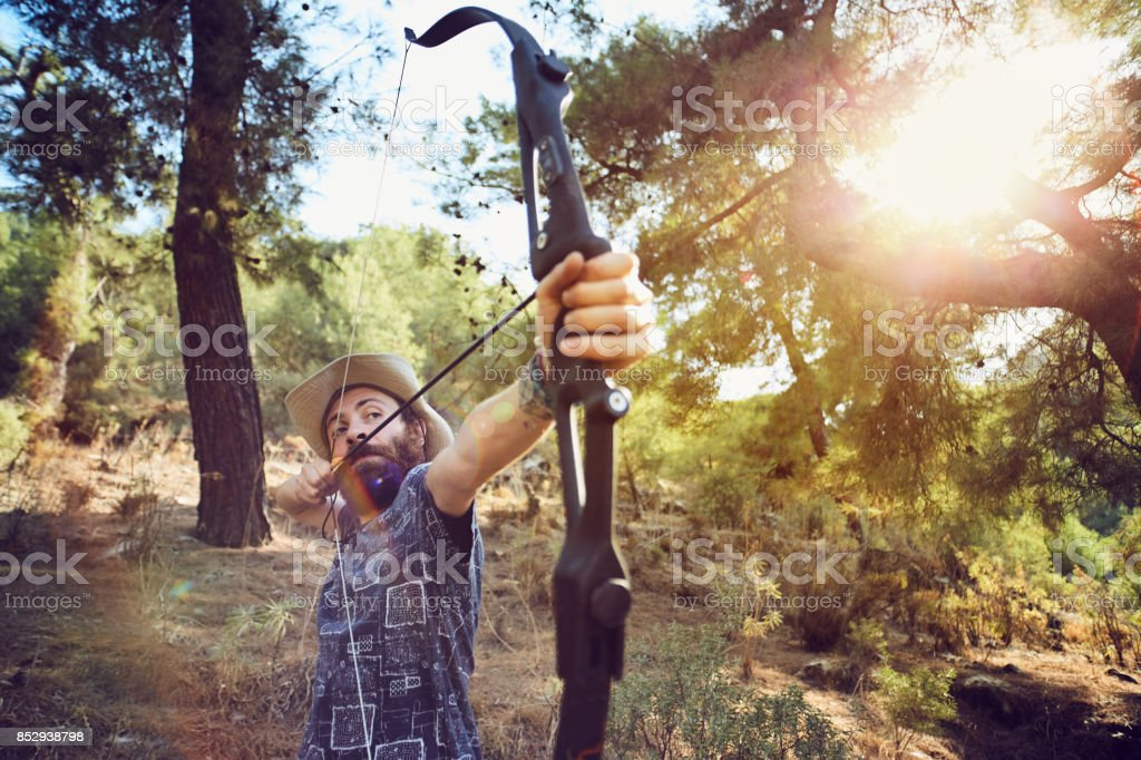 a young man is preparing to shoot with the bow in the forest stock photo