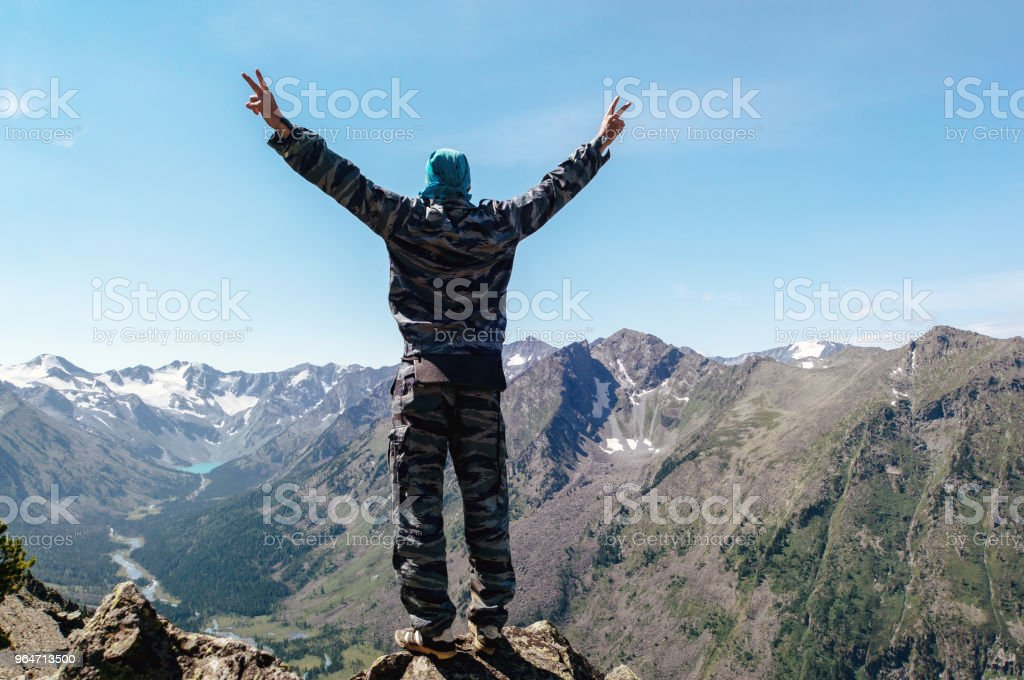 a young man standing on a hill with raised hands royalty-free stock photo