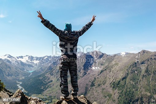 A Young Man Standing On A Hill With Raised Hands Stock Photo & More Pictures of Adult