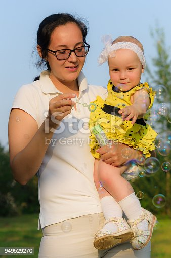 istock a young mother holding a daughter and blowing bubbles 949529270