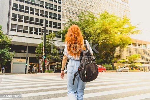 a woman crossing the pedestrian lane on avenue paulista