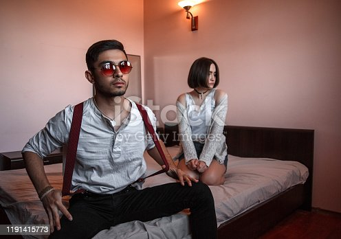 a young stylish guy in glasses and a young girl together sitting on the bed. the guy closer to the girl further. selective focus.