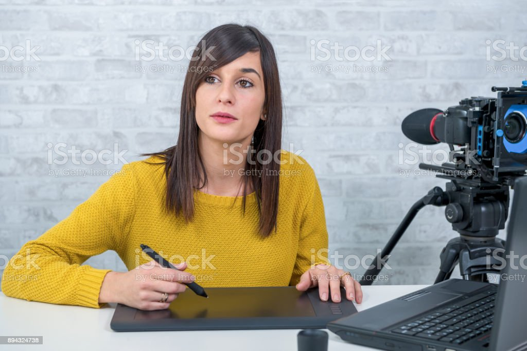 a young woman designer using graphics tablet for video editing stock photo