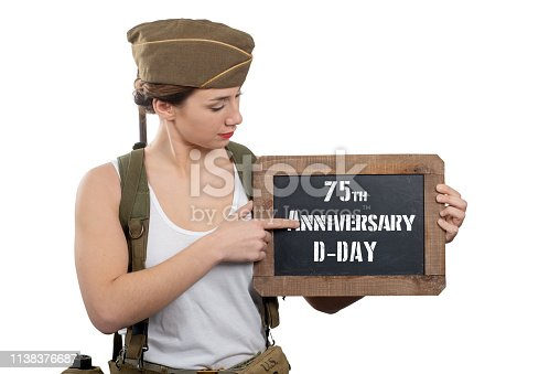 istock a young woman dressed in american ww2 military uniform showing chalkboard with d-Day anniversary 1138376687