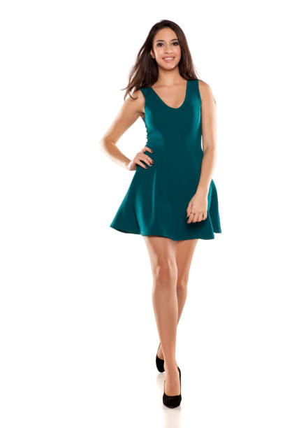 a young woman in a short turquoise dress walking stock photo