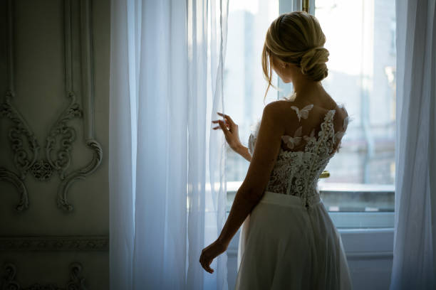 a young woman in a wedding dress and hairstyle is standing at the window, a beautiful silhouette stock photo