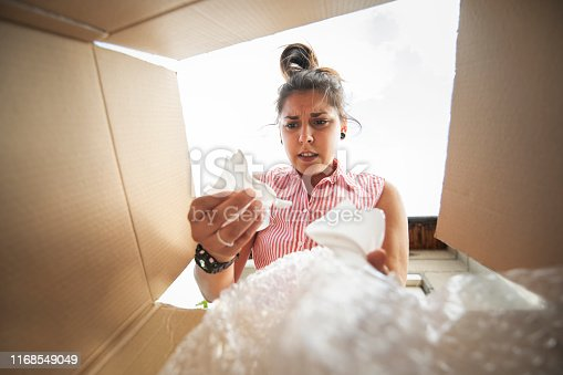 istock a young woman opens a box with a broken shipment 1168549049