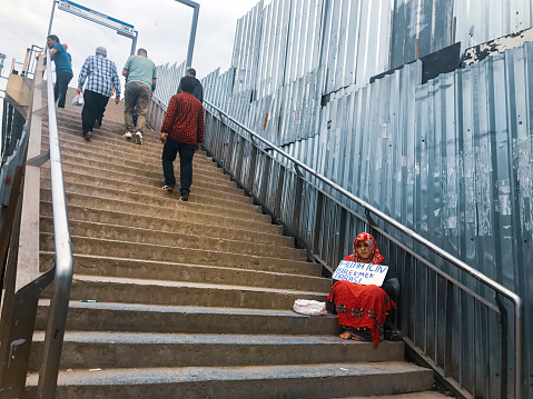 Istanbul, Turkey - June 21, 2017: a lady with traditional clothes begging and some people passing by. The text says help for a bread for god's sake. For helping panhandler asker aid human relations street city life concepts