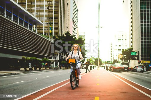 a woman on a bicycle, smiling by in são paulo