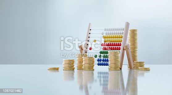 Abacus and coin stacks sitting in front of defocused background. Horizontal composition with copy space. Great use for home finances and budget concepts.