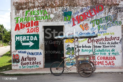 Abala, Yucatan, Mexico: A pedicab with ice cream cones parked in front vibrant wall covered with words in Abala, an indigenous village about 50 kilometers south of Merida, Mexico.