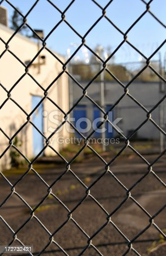 Empty jail yard.  Jail intentionally out of focus. Focus on fence.  More jail photos here: