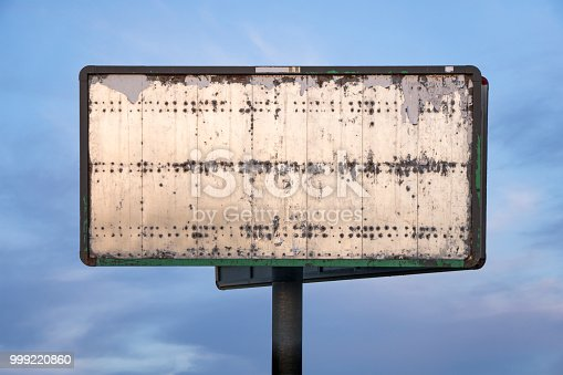 Old rusty blank advertising billboard on sky background