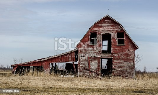 Abandoned and spooky barn with broken windows and stormy skies in the middle of the rural Midwest countryside.