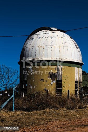 Poços de caldas, minas gerais, BRAZIL - Abandoned astronomical observatory with peeling yellow walls and white dome under a cloudless sky.