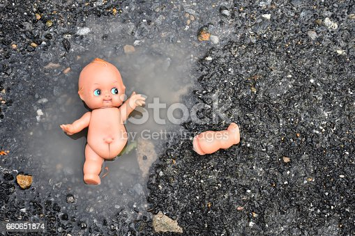 istock abandoned baby doll in the water on the road, concept for sad emotion, thriller, departed 660651874