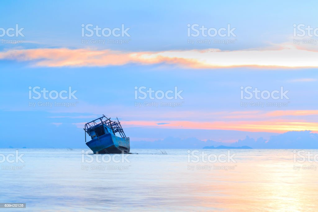 abandoned blue boat at the sea in sunset Time stock photo