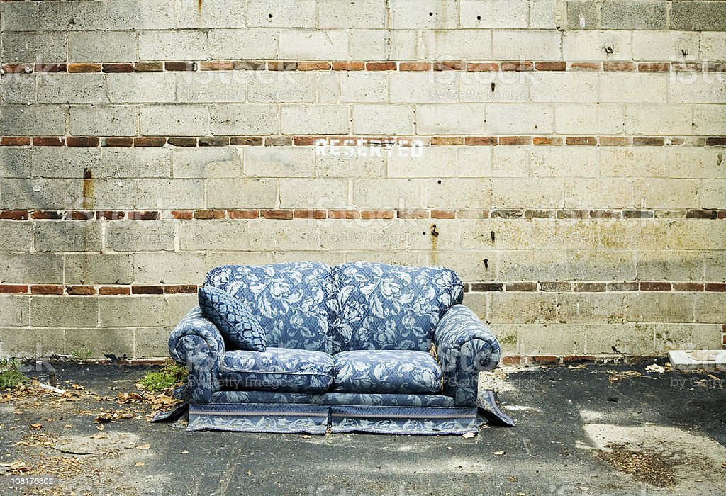 Abandoned Blue Couch Sitting Against Cement Wall Outside royalty-free stock photo