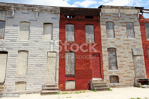 A street of abandoned and boarded up rowhouses in a blighted part of the city.