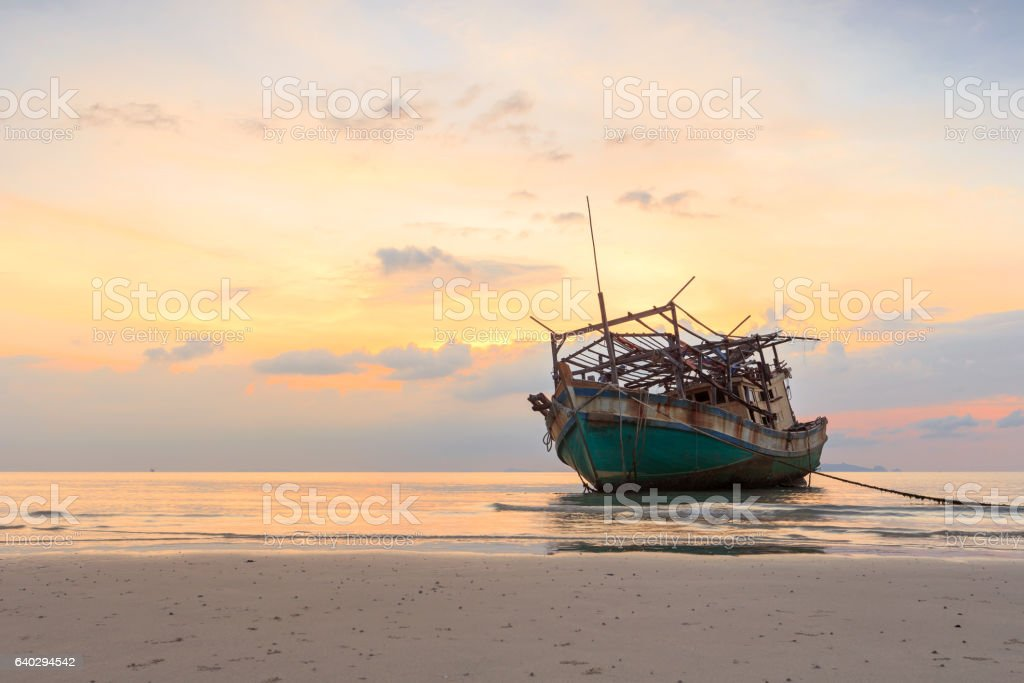 abandoned boat at beach in twilight stock photo
