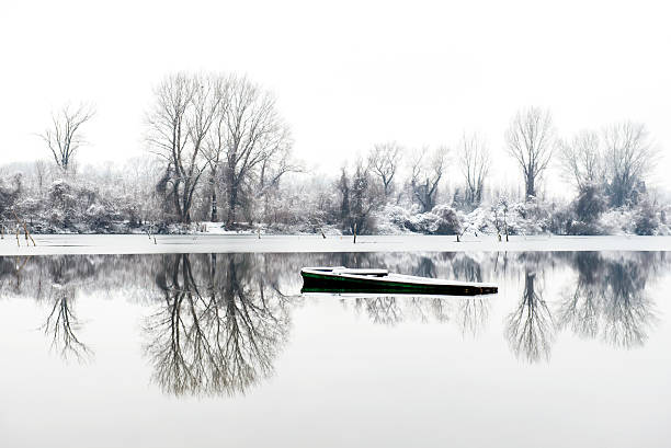 abandoned boat frozen in a lake stock photo