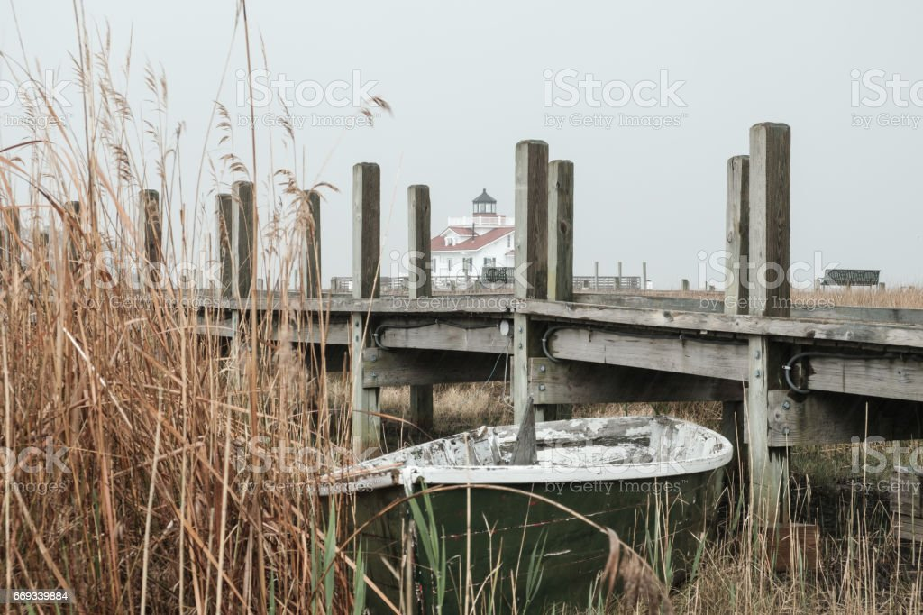 Abandoned boat sits in the marsh near the Manteo Roanoke Island Lighthouse in the rain stock photo