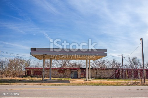 A long, low deserted and crumbling gas station without pumps along a roadside in springtime landscape