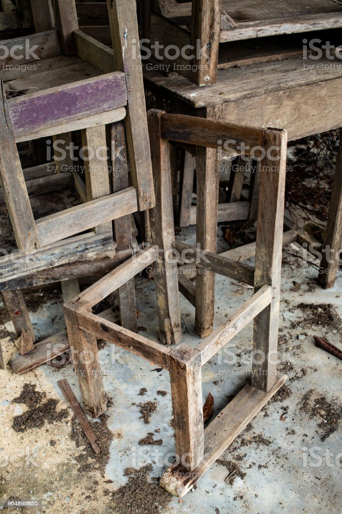 Abandoned broken vintage wooden chairs and vintage wooden desks in old school royalty-free stock photo