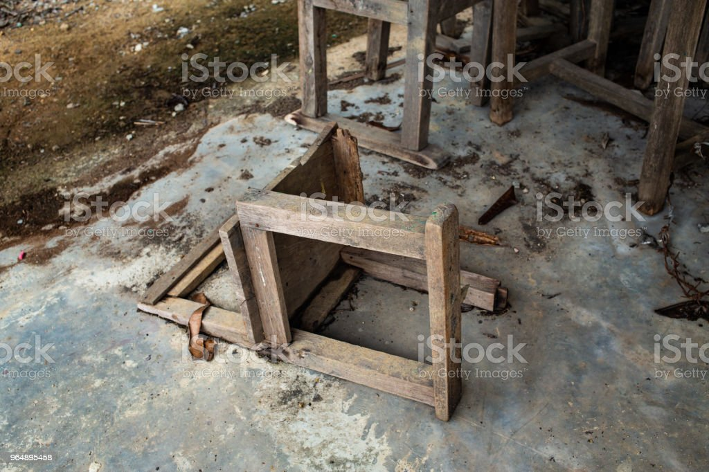 Abandoned broken vintage wooden chairs in old school royalty-free stock photo