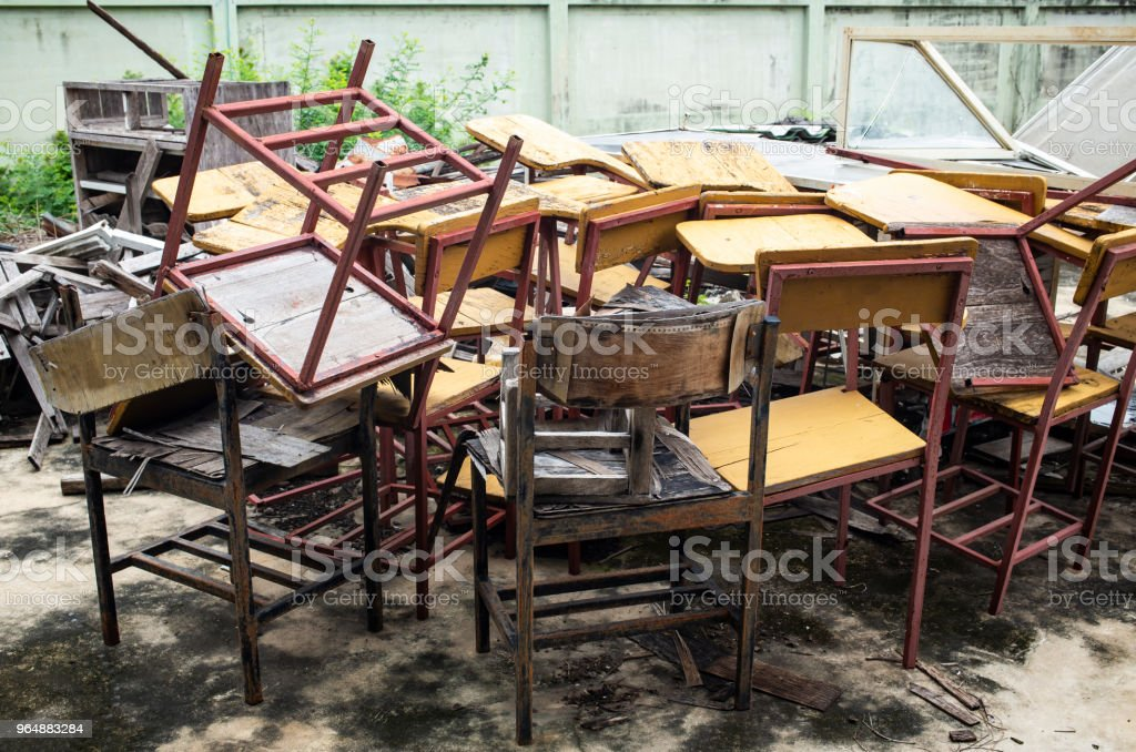Abandoned broken vintage wooden lecture chairs in old school royalty-free stock photo