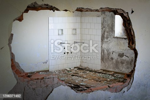 Destroyed wall that opens onto the remains of a bathroom, white tiles and rubble