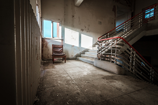 Abandoned building dark staircase in run down old hospital school with lone chair