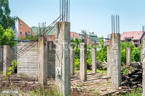 Abandoned building or house unfinished construction site with architectural details of concrete skeleton and reinforcement poles and iron or steel bars