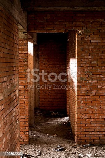 Abandoned building with brick walls. Shades and light reflections.