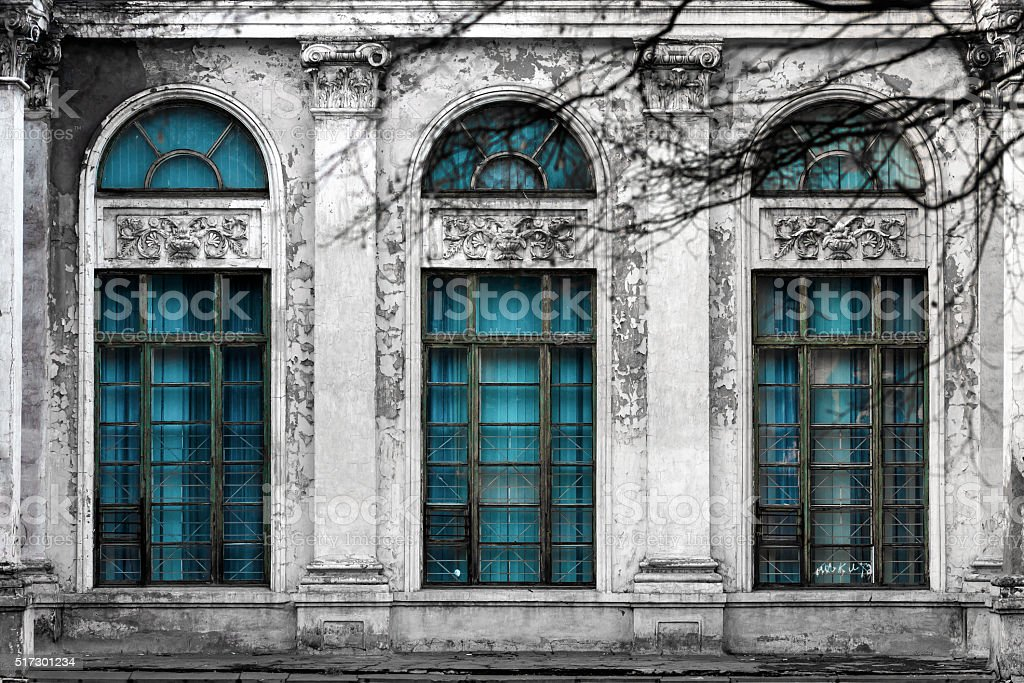 Abandoned building with three large arched windows of blue glass stock photo