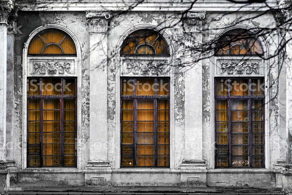 Abandoned building with three large arched windows of orange glass stock photo