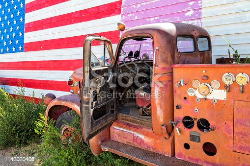 Abandoned truck standing in Seligman, American flag is visible in the background on home, Arizona, United States.